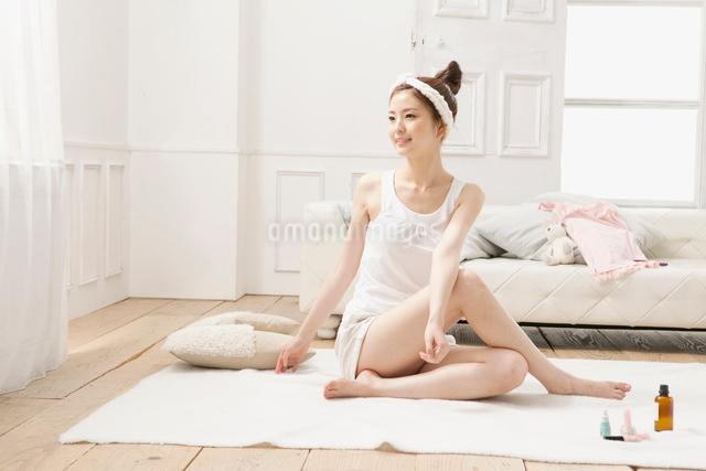 ルームウェア姿でストレッチをする女性の写真素材 [FYI01436143]