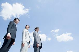 青空の下に立つビジネスマンとビジネスウーマンの写真素材 [FYI01436186]