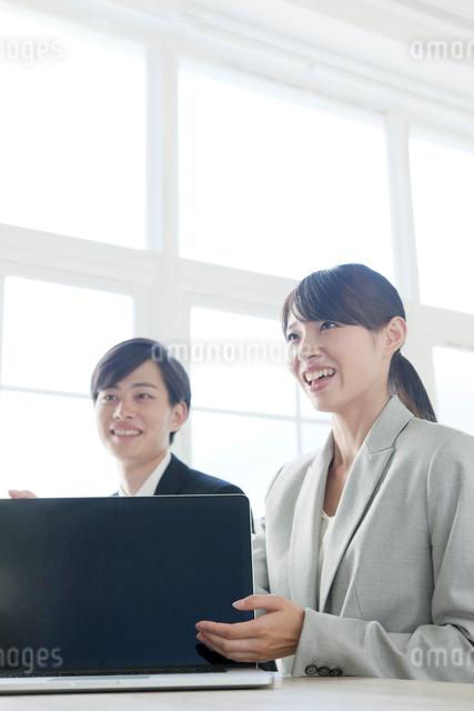 ノートパソコンを見せる打ち合わせ中のビジネスウーマンの写真素材 [FYI01436211]