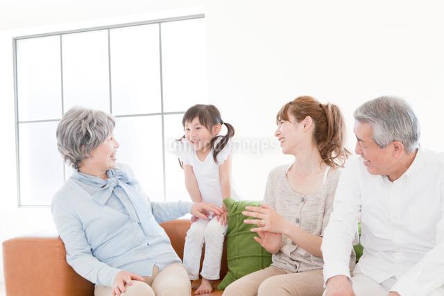 ソファでくつろぐ祖父,祖母,娘,孫娘の写真素材 [FYI01436427]