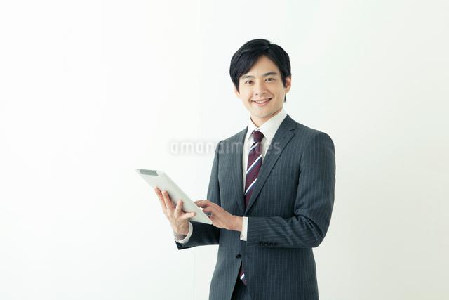 タブレットを使うスーツ姿の20代の日本人男性の写真素材 [FYI01436475]