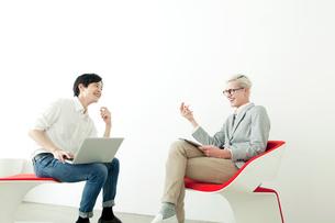 椅子に座り向かい合う20代の日本人男性と外国人男性の写真素材 [FYI01436520]