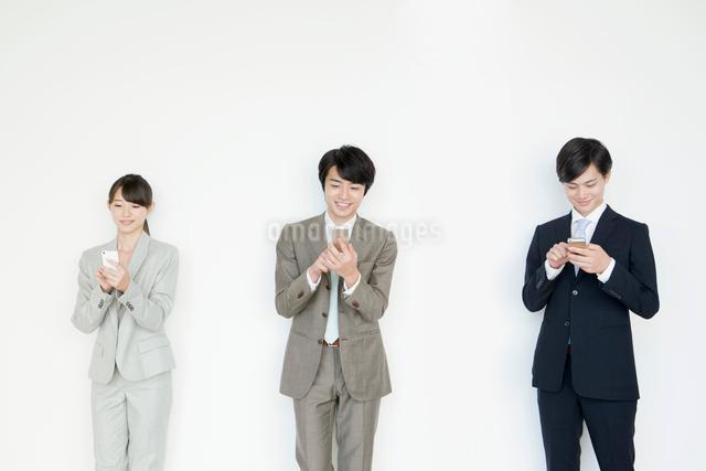 携帯電話を使うスーツ姿の男性と女性の写真素材 [FYI01436576]
