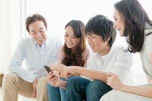 ソファーでスマートフォンを楽しむ家族の写真素材 [FYI01436583]