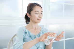 口紅を塗る中年女性の写真素材 [FYI01436588]