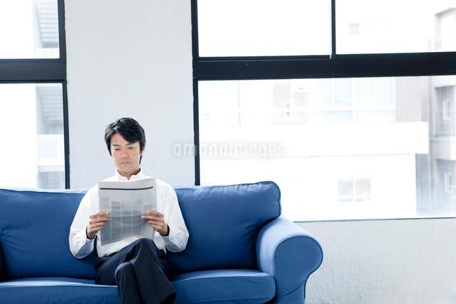 ソファーで新聞を読む男性の写真素材 [FYI01436623]