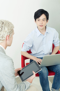 椅子に座り向かい合う20代の日本人男性と外国人男性の写真素材 [FYI01436650]