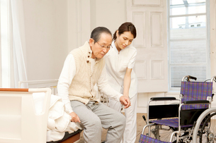 車椅子のシニア男性をフォローする女性介護士の写真素材 [FYI01436887]