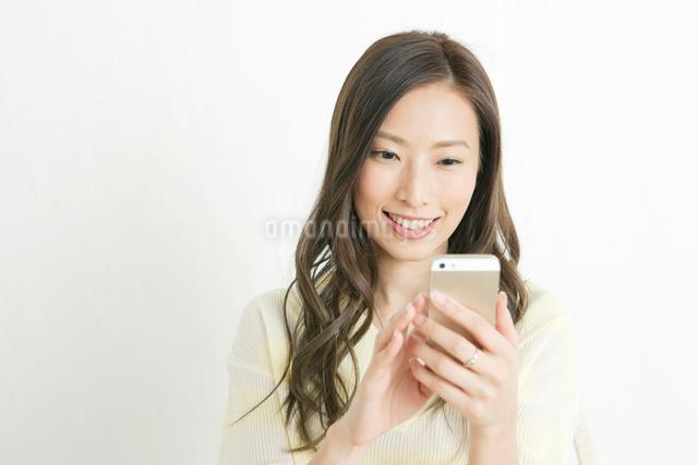スマホを操作する20代女性の写真素材 [FYI01436974]