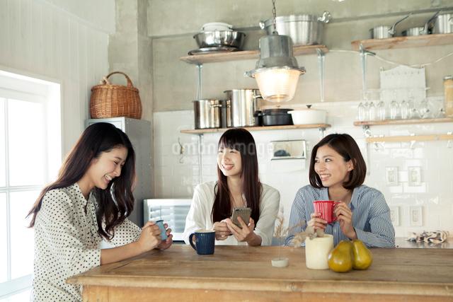 キッチンでくつろぐ20代女性3人の写真素材 [FYI01436986]