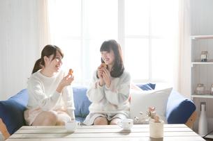 ソファーに座りながらおやつを食べる20代女性2人の写真素材 [FYI01436993]