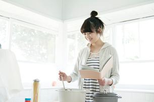 本を見ながら料理する10代女子大生の写真素材 [FYI01437009]