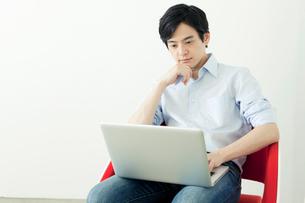 椅子に座りパソコンを使う20代の日本人男性の写真素材 [FYI01437062]