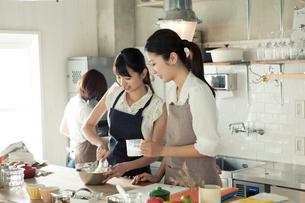 お菓子作りをする20代女性3人の写真素材 [FYI01437208]