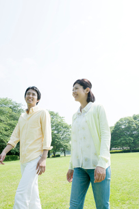 芝生を歩くカップル、の写真素材 [FYI01437221]