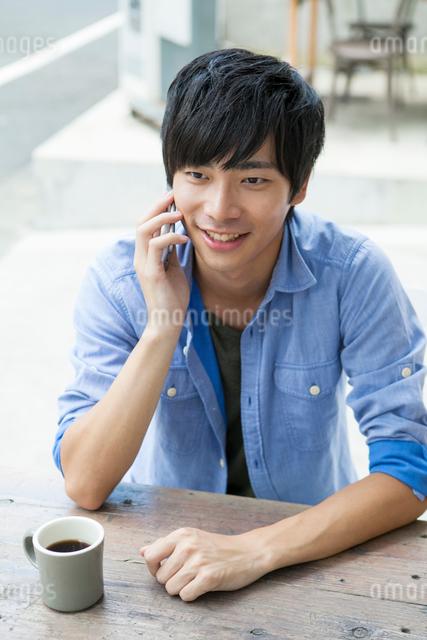 電話をする20代男性の写真素材 [FYI01437342]
