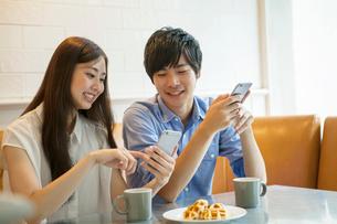 カフェでコーヒーを飲む20代男女の写真素材 [FYI01437495]