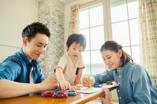 リビングで遊ぶ家族三人の写真素材 [FYI01437503]