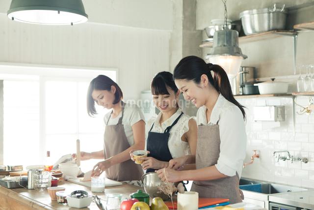 お菓子作りをする20代女性3人の写真素材 [FYI01437569]