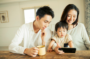 スマホを見る仲良し家族の写真素材 [FYI01437587]