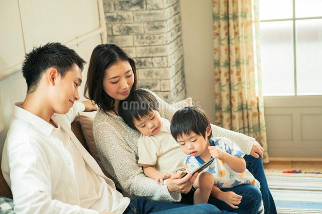 スマホを見る仲良し家族の写真素材 [FYI01437638]