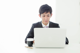 オフィスで仕事をする20代ビジネスマンの写真素材 [FYI01437785]