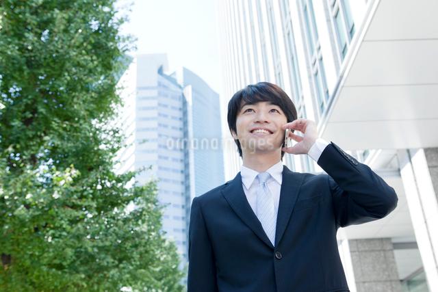 携帯電話で話すヤングビジネスマンの写真素材 [FYI01437828]