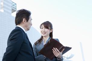 立ち話をする50代男性と20代女性のビジネスパーソンの写真素材 [FYI01437850]