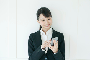 スマホを操作するスーツ姿の若い女性の写真素材 [FYI01437908]