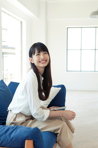 ソファーでくつろぐ20代女性の写真素材 [FYI01437946]
