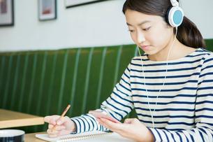 カフェで音楽を聴く20代女性の写真素材 [FYI01437967]