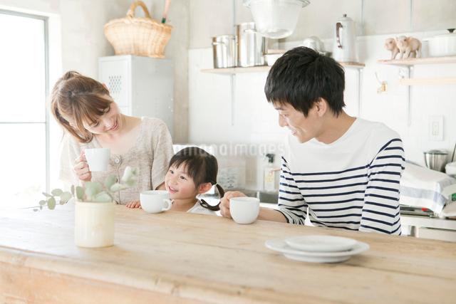 キッチンでくつろぐ夫婦と娘の写真素材 [FYI01437969]