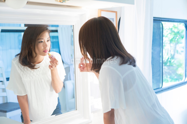 口紅を塗る20代女性の写真素材 [FYI01438055]