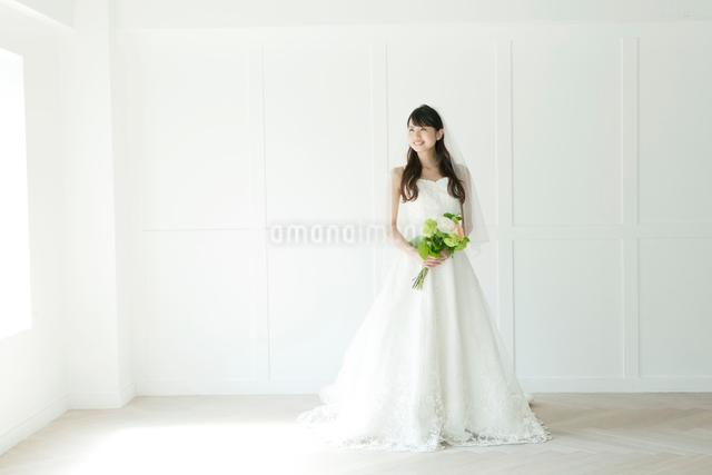 ウェディングドレス姿でブーケを持ち立っている若い女性の写真素材 [FYI01438132]