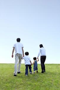 坂の芝生を登っていく家族の写真素材 [FYI01438226]