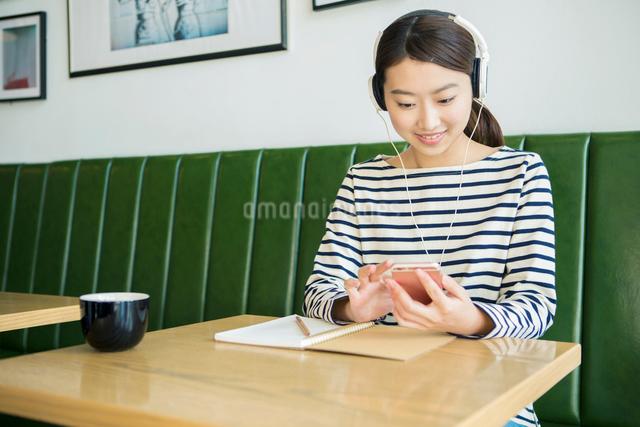 カフェで音楽を聴く20代女性の写真素材 [FYI01438238]