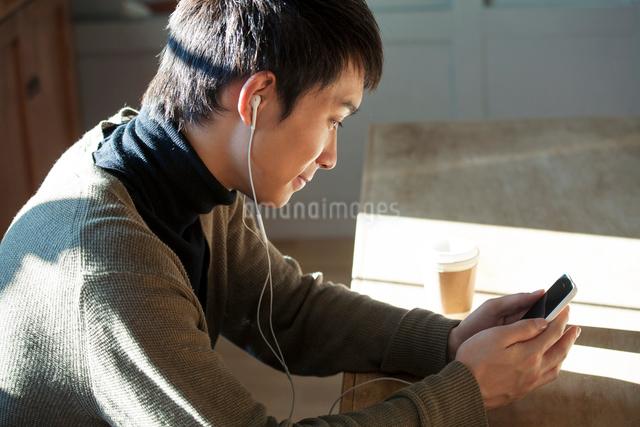 スマホで音楽を聴く20代男性の写真素材 [FYI01438337]