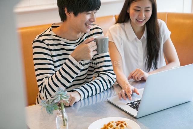 カフェでPCを使う20代男女の写真素材 [FYI01438431]