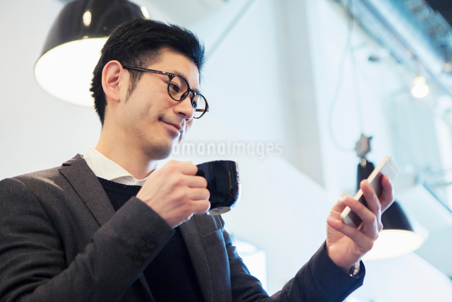 カフェでスマホを見る30代男性の写真素材 [FYI01438533]