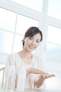 化粧水を手にとる中年女性の写真素材 [FYI01438595]