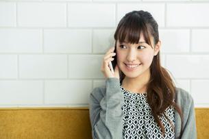 部屋で電話をする20代女性の写真素材 [FYI01438602]