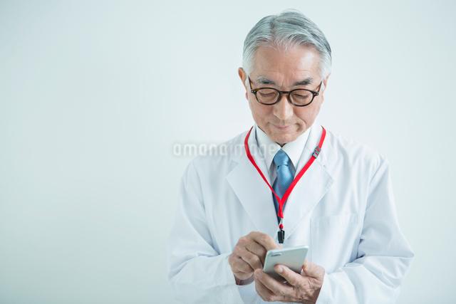 スマホを使う白衣を着た70代男性の写真素材 [FYI01438656]