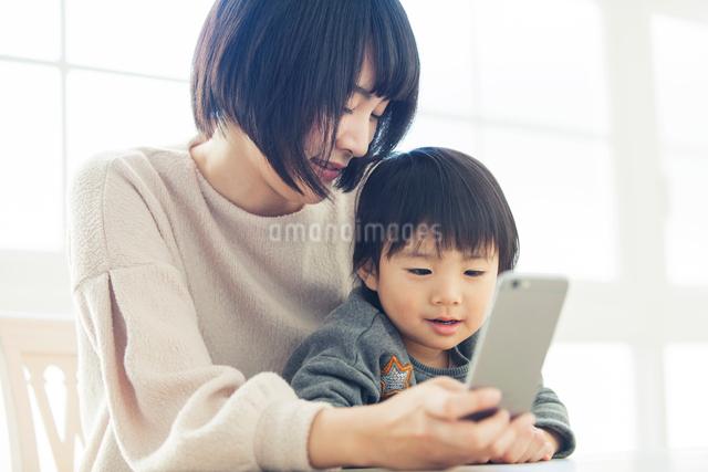 リビングで携帯を覗く親子の写真素材 [FYI01438776]