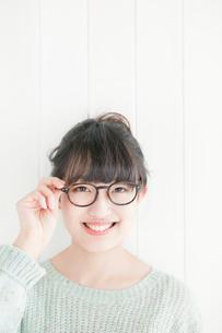 メガネのフレームを持つ笑顔の20代女性の写真素材 [FYI01438830]