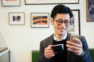 カフェでスマホを見る30代男性の写真素材 [FYI01438834]