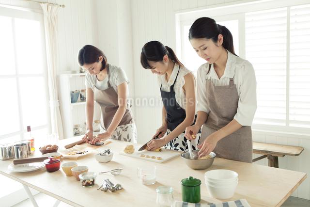 お菓子作りをする20代女性3人の写真素材 [FYI01438913]