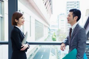 屋外で話すスーツ姿の男女の写真素材 [FYI01438916]