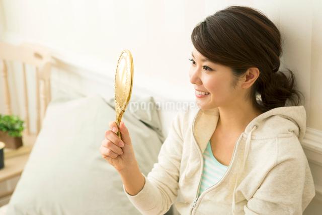 手鏡を見る笑顔の20代女性の写真素材 [FYI01439037]