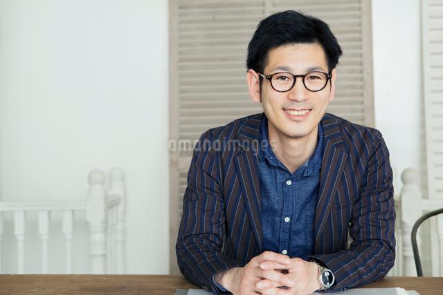 机の前で手を組む笑顔の30代男性の写真素材 [FYI01439061]