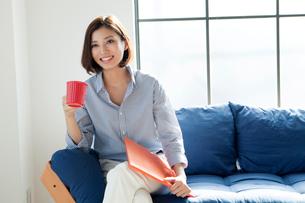 ソファーでコップを持つ20代女性の写真素材 [FYI01439064]